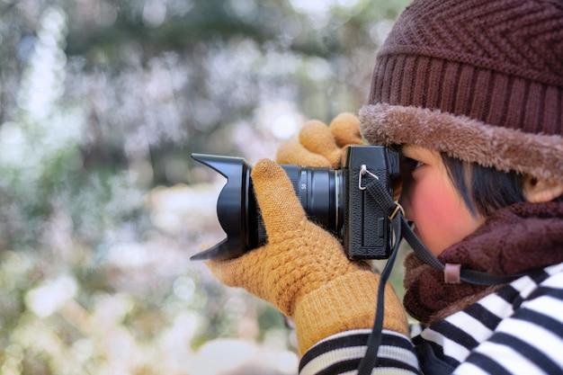 Porträt eines niedlichen kleinen mädchens im wollhut, das ein bild mit digitalkamera am wetter macht, ist kalt auf unscharfem hintergrund