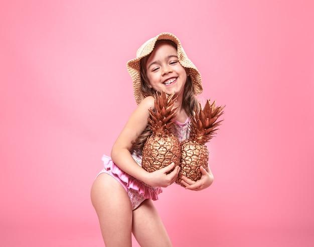 Porträt eines niedlichen kleinen mädchens in einem sommerhut, hält zwei in gold gemalte ananas, das konzept des sommers und der kreativität