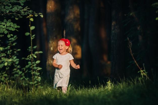 Porträt eines niedlichen kleinen mädchens läuft auf einem grünen rasen in einem wald. ein glückliches kind lacht und lächelt. sonniger wald, ein sonnenstrahl.