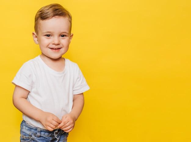 Porträt eines niedlichen lachenden kleinen jungen auf gelbem hintergrund. speicherplatz kopieren.