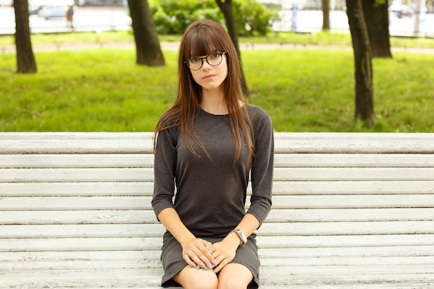 Porträt eines niedlichen mädchens mit brille, sitzend auf einer bank auf der straße im park.