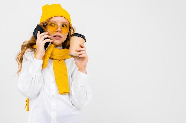Porträt eines niedlichen mädchens mit einer wintermütze und einem schal mit einer tasse kaffee und einem telefon nahe dem ohr auf weiß mit kopienraum