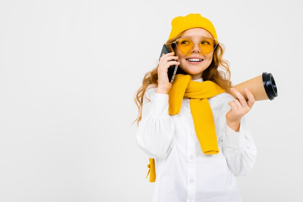Porträt eines niedlichen mädchens mit einer wintermütze und einem schal mit einer tasse kaffee und einem telefon nahe dem ohr auf weiß