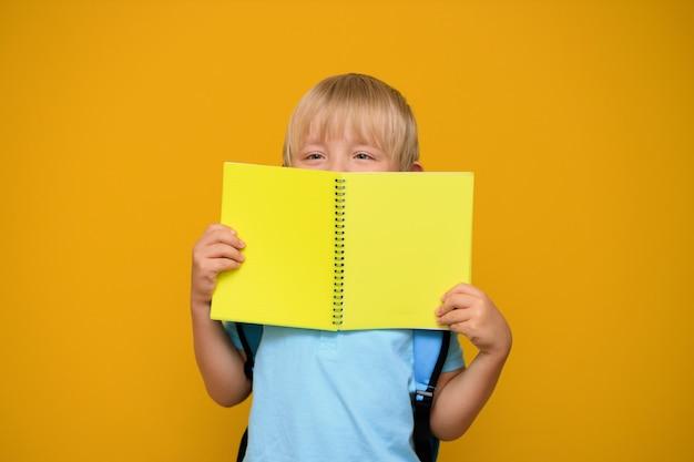 Porträt eines niedlichen schuljungen 6 jahre alt mit einem hellen rucksack auf einem gelben hintergrund. zurück zur schule.