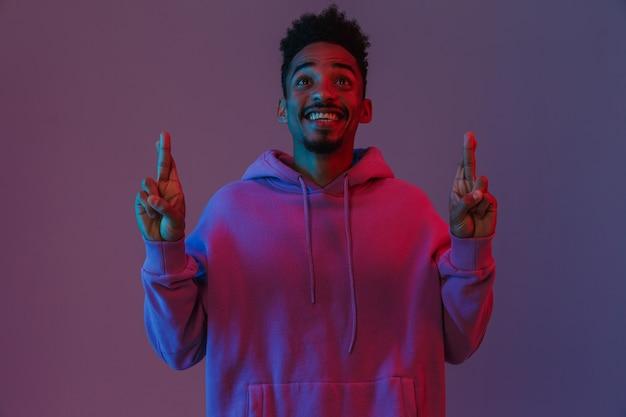 Porträt eines optimistischen afroamerikanischen mannes in farbenfrohem hoodie, der mit gekreuzten fingern isoliert über violetter wand posiert