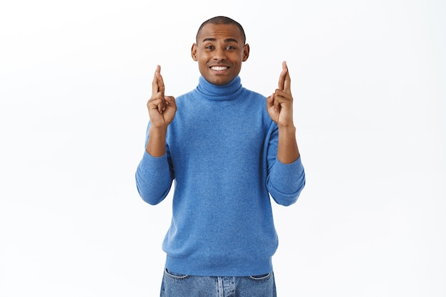 Porträt eines optimistischen, hoffnungsvollen afroamerikaners, der die daumen für viel glück kreuzt und die ergebnisse erwartet