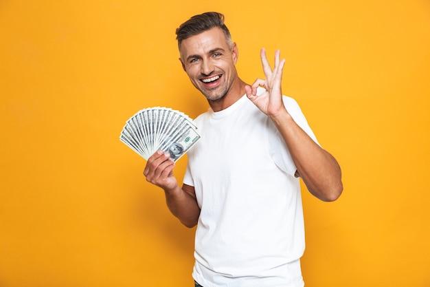 Porträt eines optimistischen kerls der 30er jahre im weißen t-shirt, der lächelt und einen haufen geld isoliert auf gelb hält