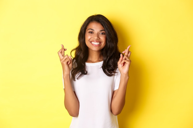 Porträt eines optimistischen, lächelnden afroamerikanischen mädchens, das die finger für viel glück kreuzt und den wunsch macht, auf gelbem hintergrund stehend.