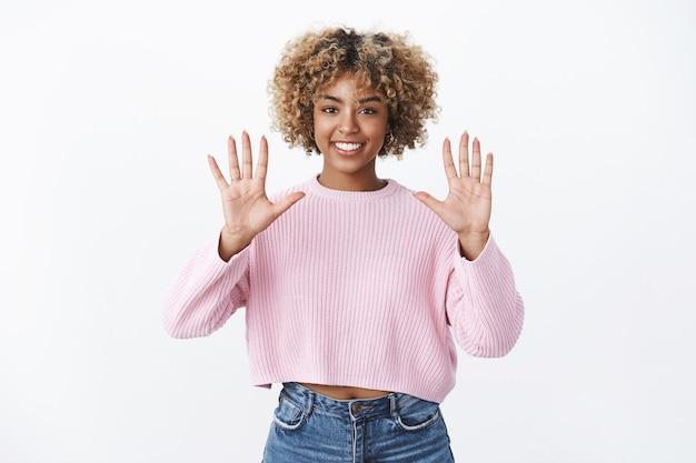 Porträt eines optimistischen und fröhlichen afroamerikanischen, stilvollen mädchens mit blondem afro-haarschnitt, das erfreut und zuversichtlich lächelt, als er die hände hebt und die nummer zehn zeigt, die gegen die weiße wand posiert