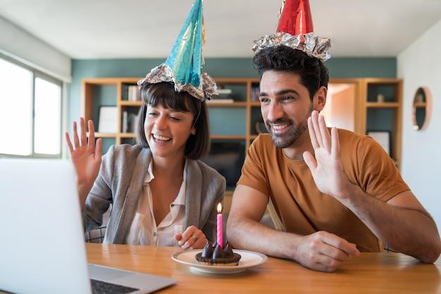 Porträt eines paares, das geburtstag auf einem videoanruf mit einem laptop von zu hause feiert. paar feiert geburtstag online in quarantänezeit. neues normales lifestyle-konzept.