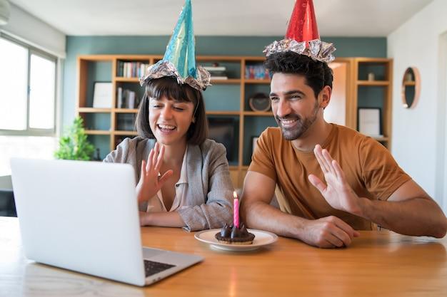 Porträt eines paares, das geburtstag auf einem videoanruf mit einem laptop von zu hause feiert