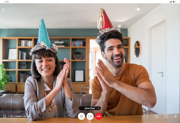 Porträt eines paares, das geburtstag auf einem videoanruf von zu hause feiert. paar feiert geburtstag online in quarantänezeit. neues normales lifestyle-konzept.