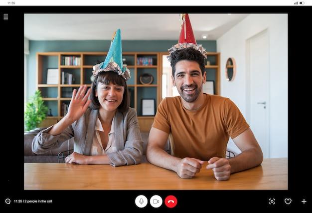 Porträt eines paares, das geburtstag bei einem videoanruf von zu hause aus feiert. paar feiert geburtstag online in quarantänezeit. neues normales lifestyle-konzept.