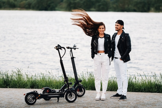 Porträt eines paares, das in der nähe von elektrorollern sitzt und zeit in der natur zusammen genießt, zwei liebhaber auf elektrorollern. leute auf rollern.
