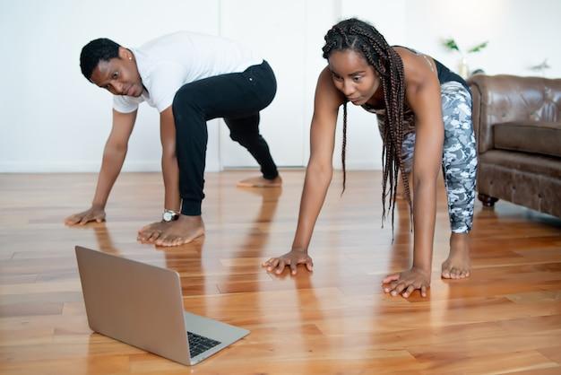 Porträt eines paares, das zusammen übung macht und video-tutorial auf laptop sieht, während zu hause bleibt. sportkonzept. neues normales lifestyle-konzept.
