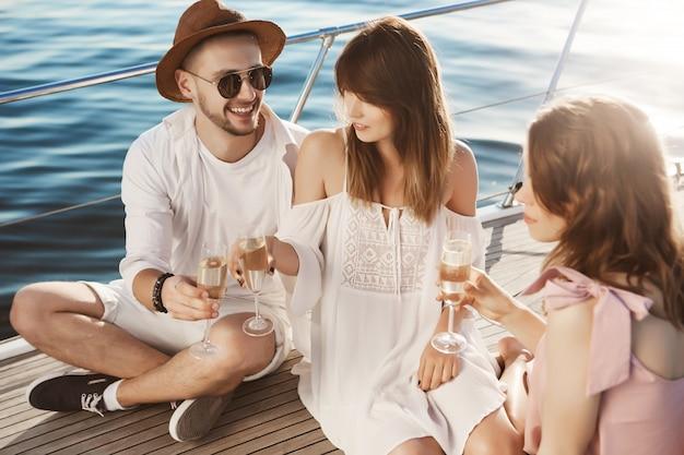 Porträt eines paares und ihres freundes, die auf einer yacht sitzen, trinken und fröhlich zeit verbringen. erwachsene nippen champagner in trendigen kleidern während des luxusurlaubs