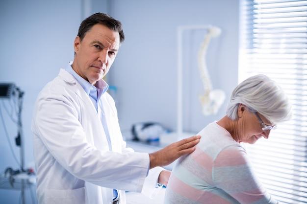 Porträt eines physiotherapeuten, der einem älteren patienten eine rückenmassage gibt