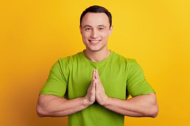 Porträt eines plädierenden positiven kerls, der händchen hält, bittet um hilfe auf gelbem hintergrund