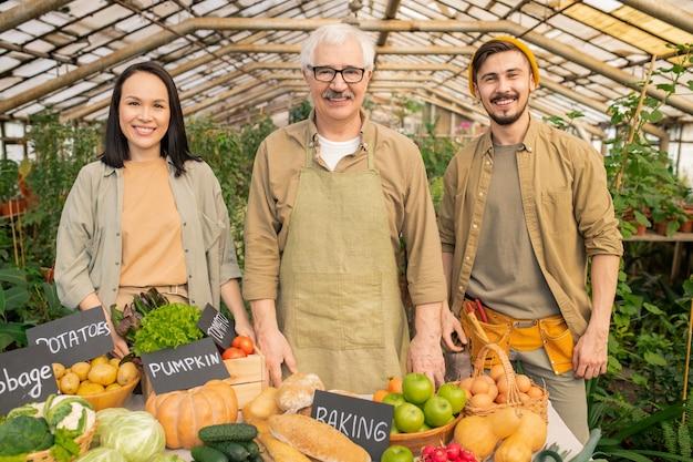 Porträt eines positiven älteren landwirts in der schürze, die bio-lebensmittel mit jungen assistenten auf dem bio-markt verkauft