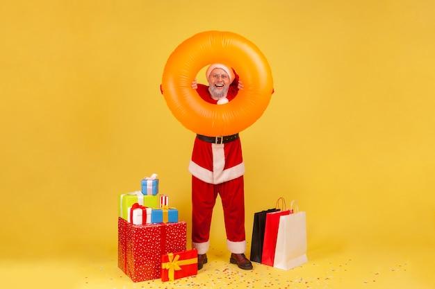 Porträt eines positiven älteren mannes mit grauem bart, der ein weihnachtsmann-kostüm mit gummiring trägt und mit geschenkboxen und einkaufstüten steht. innenstudio erschossen auf gelbem hintergrund.