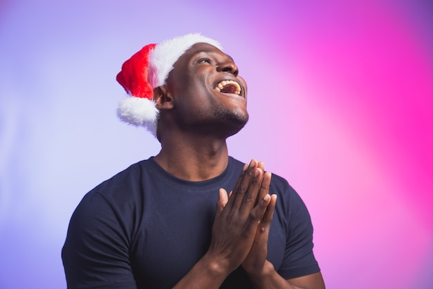 Porträt eines positiven afroamerikaners lächelnder mann in weihnachtsmütze und lässigem t-shirt auf buntem