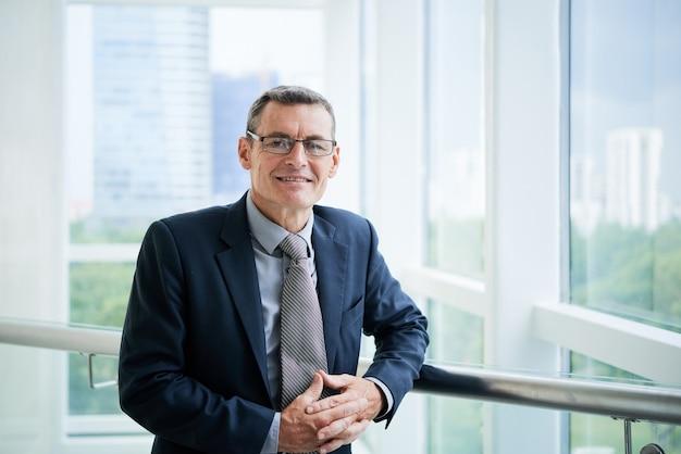 Porträt eines positiven, erfolgreichen, reifen kaukasischen unternehmensleiters in gläsern, die auf dem bürobalkon stehen
