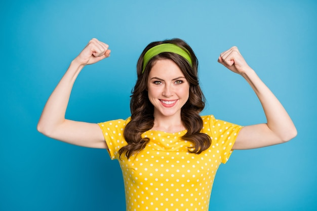 Porträt eines positiven fröhlichen mädchens, das ihre handmuskeln zeigt, tragen polka-dot-kleidung einzeln auf blauem hintergrund