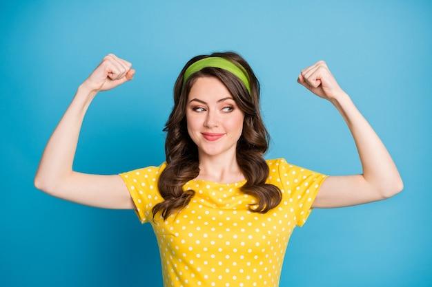 Porträt eines positiven fröhlichen mädchens, das ihre muskeln auf blauem hintergrund einzeln auf blauem hintergrund interessiert
