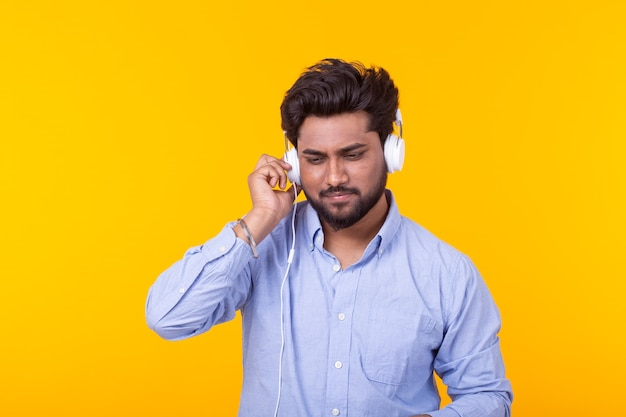 Porträt eines positiven jungen indischen mannes mit einem bart, der ein hörbuch auf gelbem raum hört