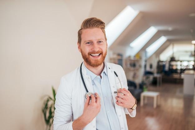 Porträt eines positiven rothaarigedoktors, lächelnd an der kamera.