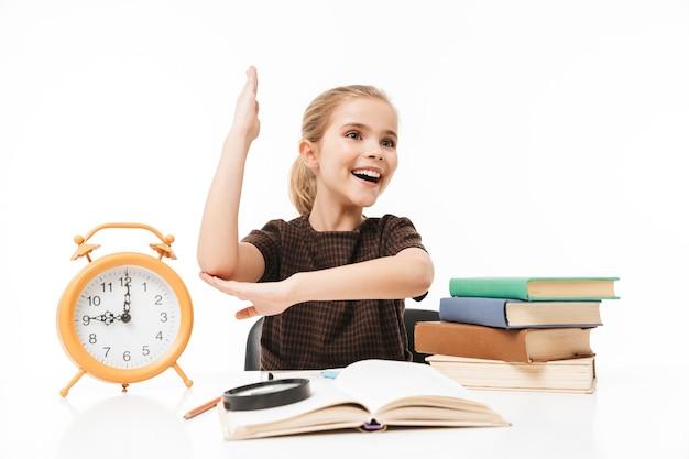 Porträt eines positiven schulmädchens mit großem wecker auf dem schreibtisch, der bücher in der klasse studiert und liest, isoliert über weißer wand