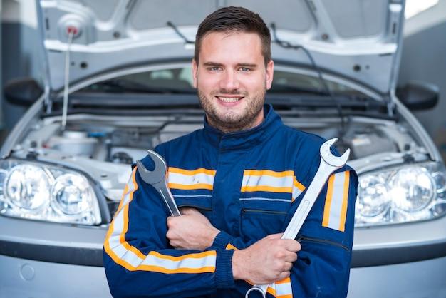 Porträt eines professionellen gutaussehenden automechanikers, der schraubenschlüssel vor dem automobil mit geöffneter motorhaube hält