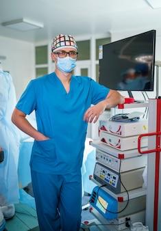 Porträt eines professionellen medizinischen assistenten in chirurgischer maske in der nähe von medizinischen geräten. moderner krankenhaus-operationssaal.
