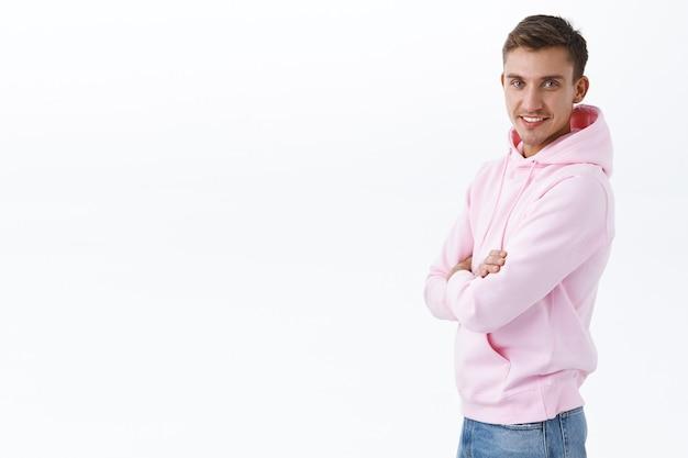 Porträt eines professionellen, selbstbewussten und enthusiastischen blonden, stylischen mannes in rosa hoodie, stehendem profil und wenden sie sich mit strahlendem lächeln an die kamera, kreuzen sie die brust stolz und selbstbewusst