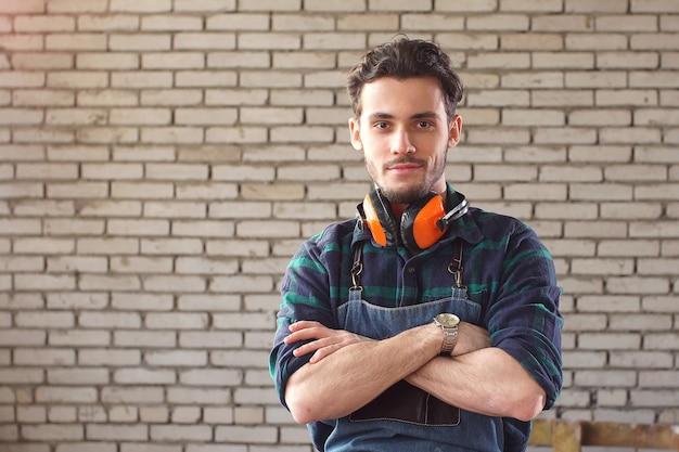 Porträt eines professionellen tischlers in seiner werkstatt.