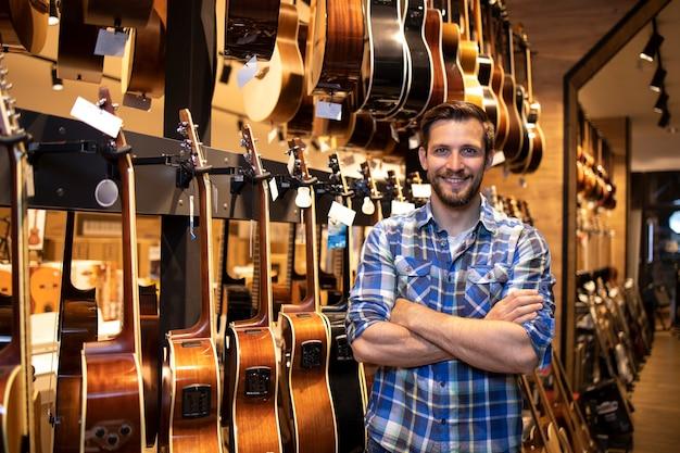 Porträt eines professionellen verkäufers, der im musikladen steht und gitarreninstrumente verkauft.
