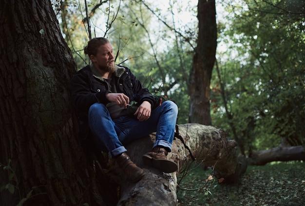 Porträt eines rauchenden jungen bärtigen abenteurers, der sich im herbstwald entspannt und eine zigarette hält