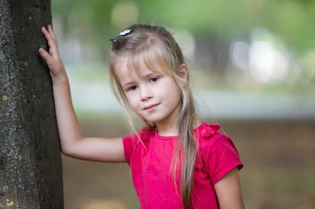 Porträt eines recht kleinen kindermädchens, das draußen nahe großem baumstamm im sommerpark steht.