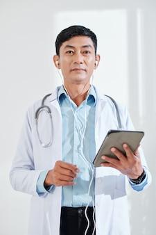 Porträt eines reifen allgemeinarztes mit digitaler tablette und ohrhörern
