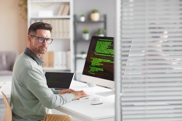 Porträt eines reifen entwicklers, der nach vorne schaut, während er am tisch mit dem computer in der softwareentwicklungsfirma arbeitet