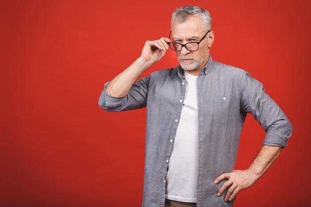 Porträt eines reifen ernsten geschäftsmannes mit gekreuzten händen, die brille lokalisiert gegen roten hintergrund tragen. schließen sie herauf gesicht des glücklichen erfolgreichen geschäftsmannes.