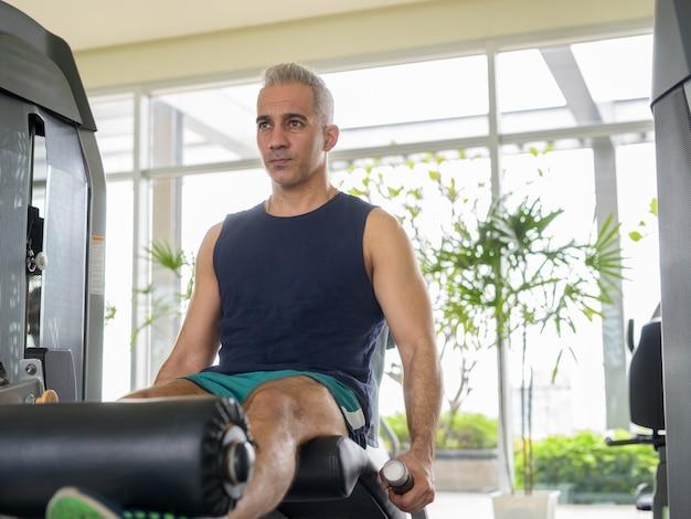 Porträt eines reifen, gutaussehenden persischen mannes mit grauem haar, der im fitnessstudio trainiert
