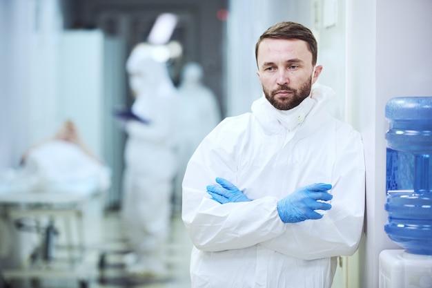 Porträt eines reifen männlichen arztes in uniform, der die kamera anschaut, während er im krankenhausflur steht