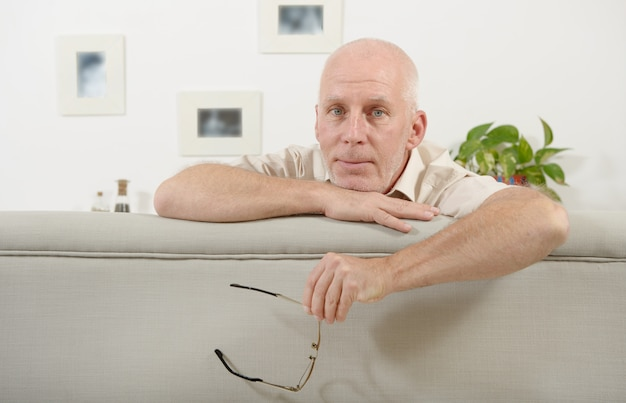 Porträt eines reifen mannes, der auf sofa sitzt