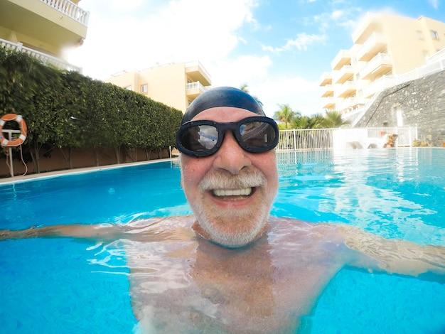 Porträt eines reifen mannes, der lächelt und die kamera im pool anschaut und allein spaß hat - training und schwimmen glücklich - nahaufnahme des gesichts eines glücklichen seniors