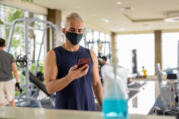 Porträt eines reifen persischen mannes mit maske zum schutz vor dem ausbruch des corona-virus, soziale distanzierung im fitnessstudio