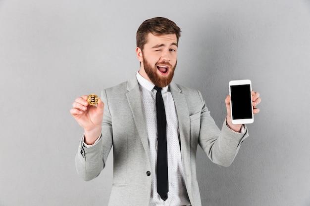 Porträt eines reizend geschäftsmannes, der bitcoin hält
