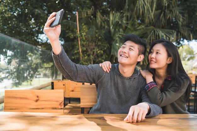 Porträt eines reizenden asiatischen paares, das gute zeit hat und ein selfie mit handy im café nimmt.