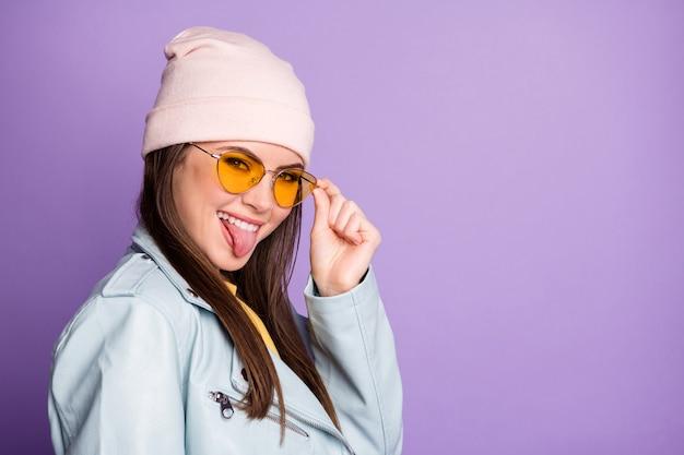 Porträt eines reizenden, charmanten, positiven teenager-mädchens genießen herbst-herbst-ferienwochenende zeigen zunge heraus touch-spezifikationen tragen ein gut aussehendes outfit einzeln auf violettem farbhintergrund