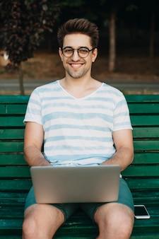 Porträt eines reizenden jungen männlichen freiberuflers, der kamera lachend betrachtet, während er an seinem laptop im freien im park auf einer bank arbeitet.